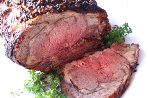 Slice of prime rib resting on a platter beside the standing rib. This picture shows the medium-rare interior of the roast.