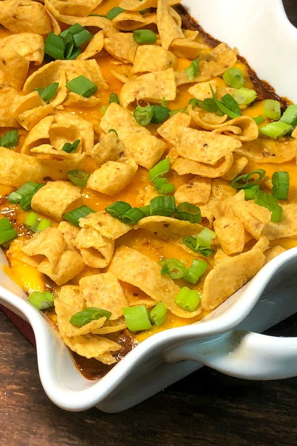 Attention Tamale Fans! Whip up this warm dip in mere minutes for your next gathering. Your guests will love these beef tamales, smothered in chili cheese-y goodness, topped with a crunch. Easy to make, easy to serve, and easy to devour! #Tamale #Dip #Chili #Cheese