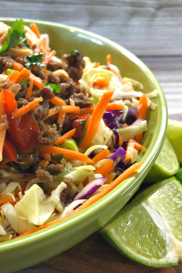 Side view of an Asian beef bowl with vegetable slow and limes.
