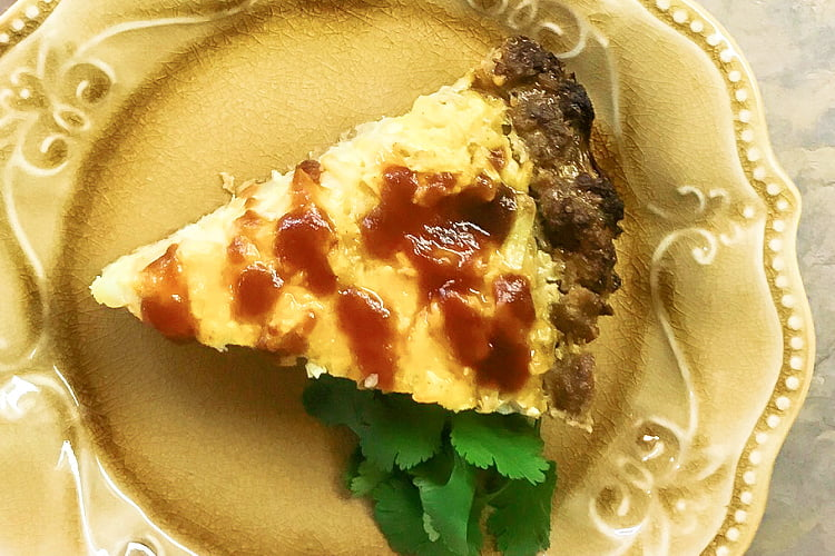 Overhead shot of a piece of Cheesy Hashbrown Meatloaf Pie on a plate.