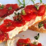 Who knows how many times we've made this easy appetizer when there's tons of homegrown tomatoes coming in from the garden! These Tomato Crostini combine the crispy/chewy texture of the bread with the creamy feta spread and the luscious vine-ripened tomatoes with fresh basil.  #HomegrownTomatoes #Tomatoes #Basil #Appetizer #Feta