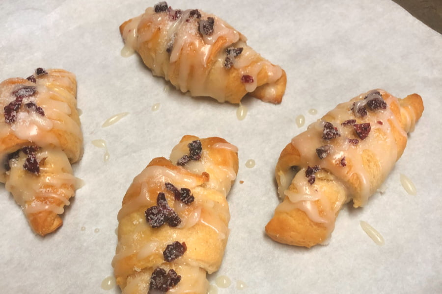 Baking sheet of baked crescent rolls that are filled with dried cranberries and chopped walnuts, then drizzled with a powdered sugar glaze.