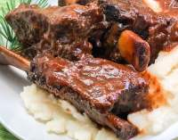 A trio of beef short ribs with sauce on a bed of mashed potatoes.
