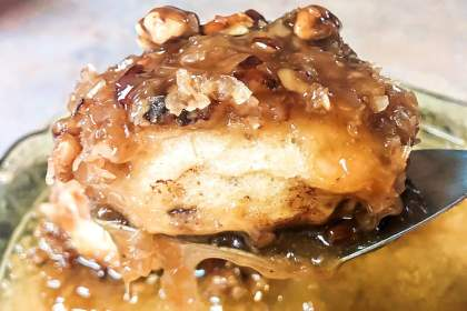 A caramel pecan sticky bun being lifted from the pan on a spatula.