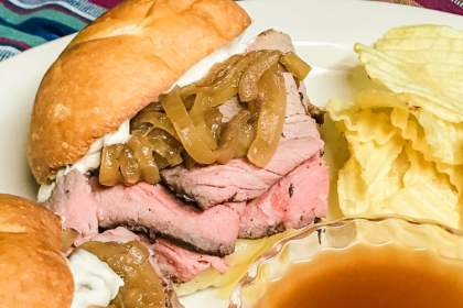 Sliced roast beef with caramelized onions piled on a bun.