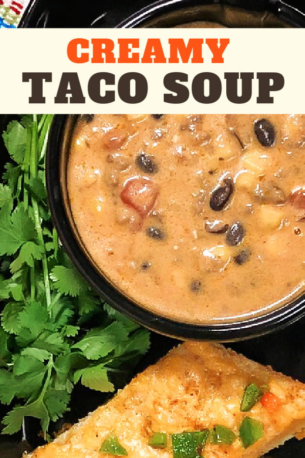 A bowl of creamy taco soup alongside a slice of Mexican cheese bread.