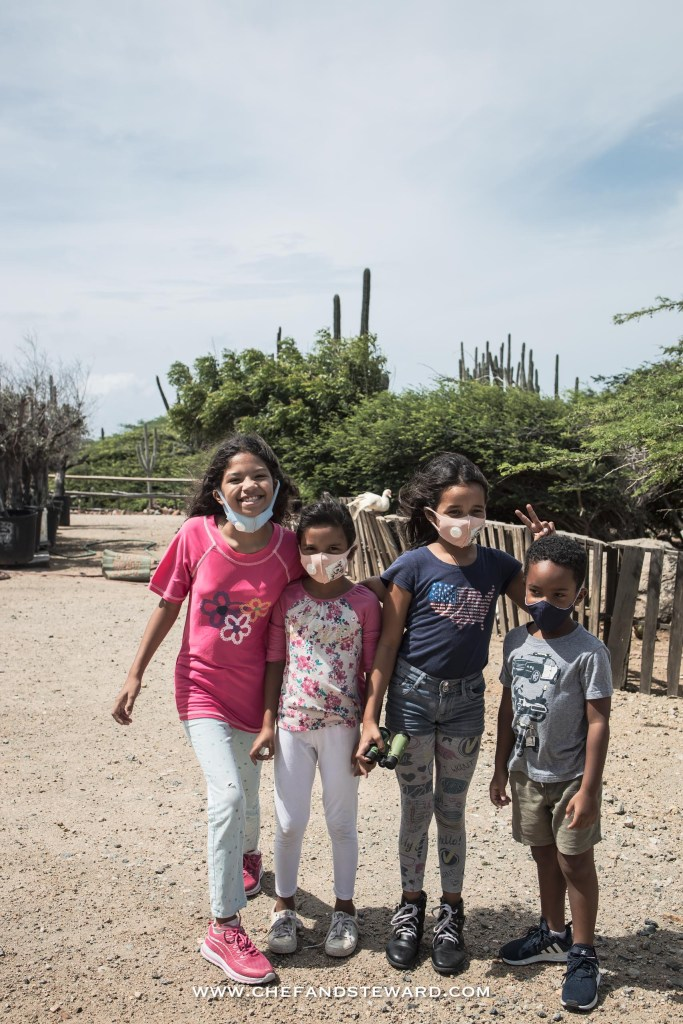 Four children standing in masks at the Aruba Ostrich farm tour for what to do in Aruba
