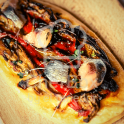 Spanish flatbread with roasted vegetables on top.