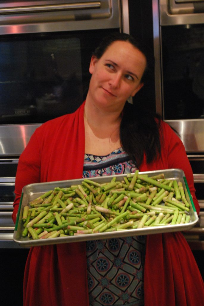 Woman holding tray of Asparagus