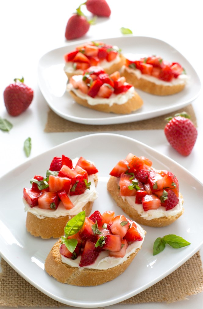 baguette topped with mascarpone, strawberries and basil on white plate