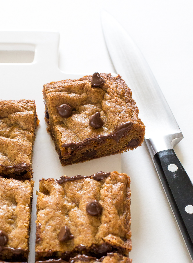 chocolate chip blondie cut into square on white cutting board next to knife