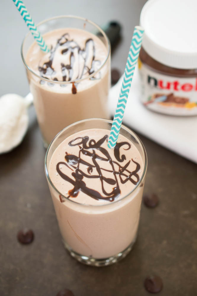 2 Milkshakes with chocolate swirled on top and blue chevron paper straws. Jar of nutella in background.
