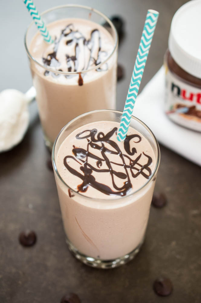 2 Peanut Butter and Nutella Milkshakes with chocolate swirled on top and blue chevron paper straws. Jar of nutella in background.
