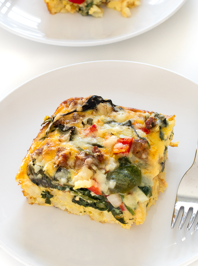 slice of egg bake with veggies on white plate next to fork