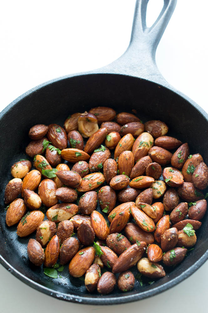 top shot of roasted almonds in black skillet with cilantro flakes