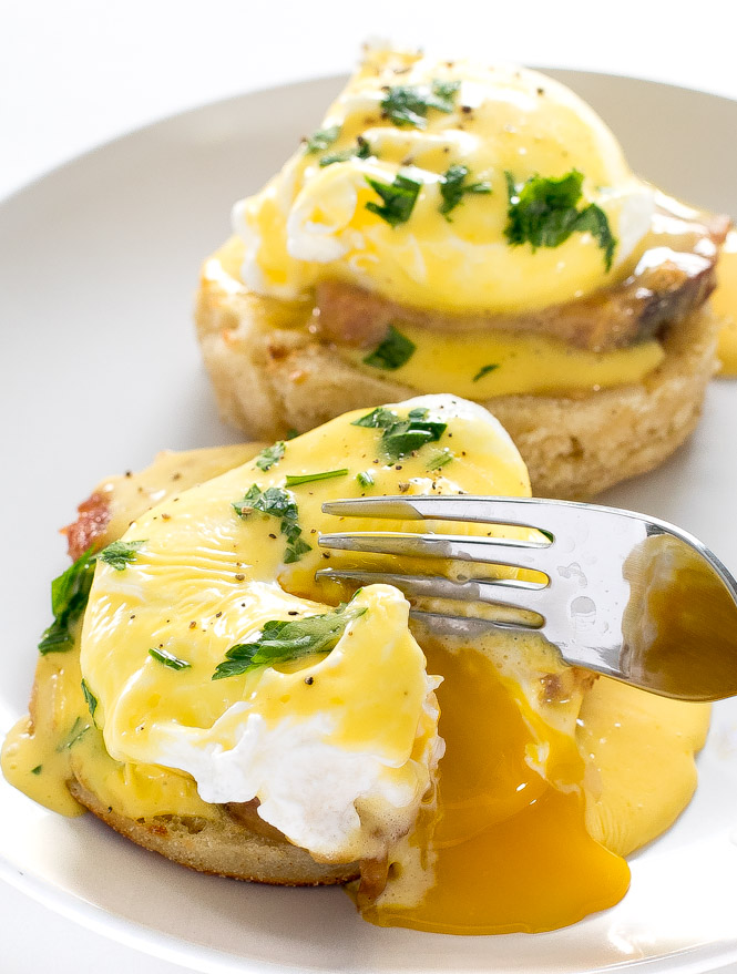 Fork cutting into poached eggs on english muffins and ham, topped with Hollandaise sauce, on circular white plate