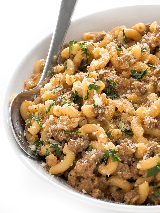 Homemade hamburger helper in white bowl with spoon.