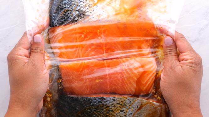 Marinating Honey Sriracha Salmon in a large ziplock bag