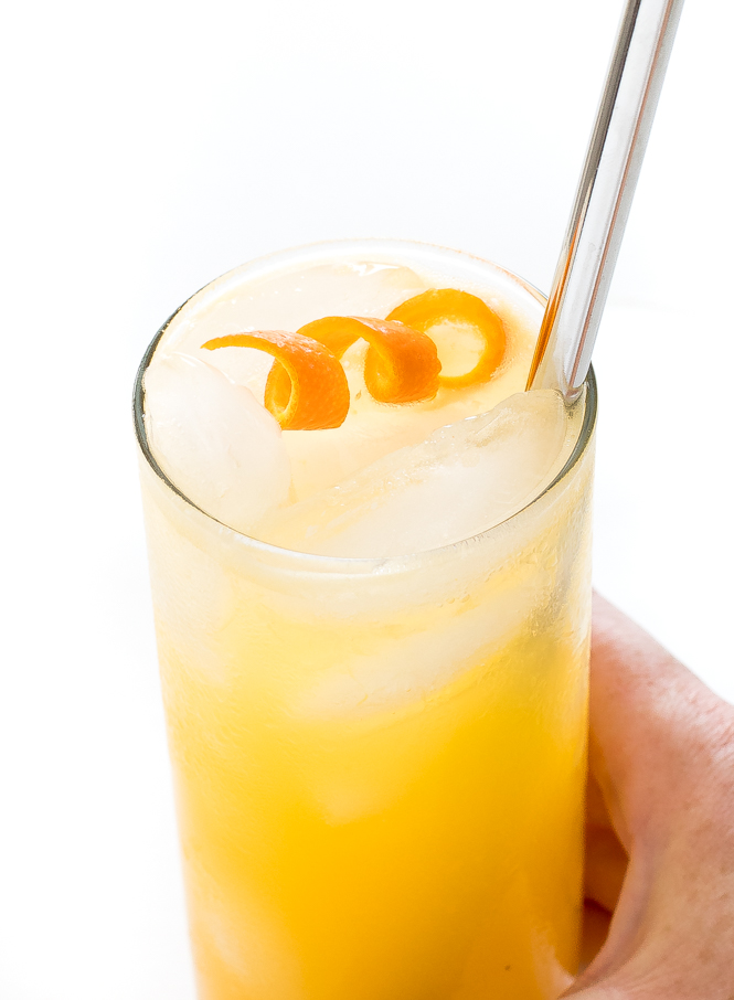 Hand holding an orange crush cocktail in hand