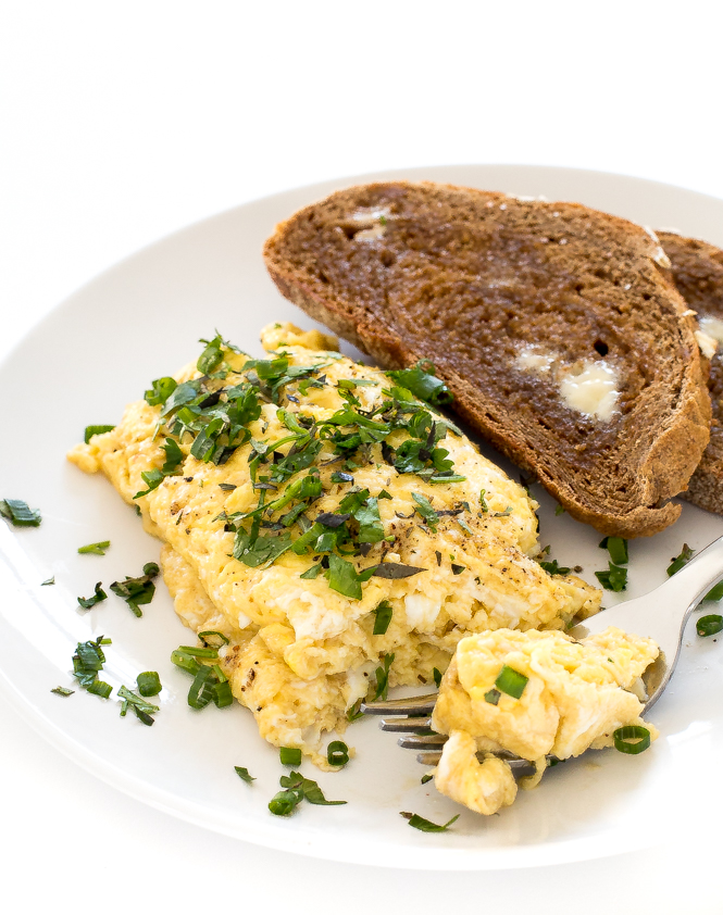 scrambled eggs and toast on round white plate with silver fork
