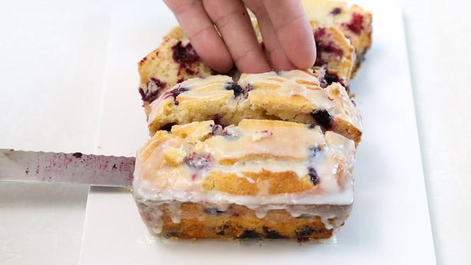 Hand taking a slice of homemade lemon blueberry bread sitting on white dish beside bread knife