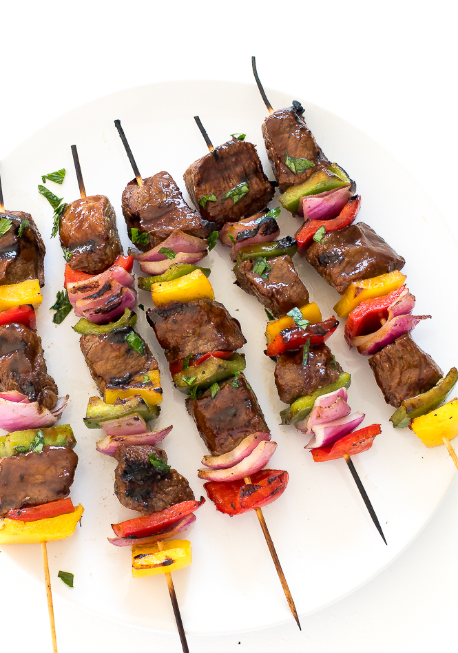 close up of grilled steak kabobs garnished with parsley