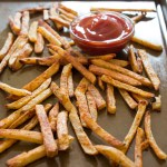 Baked french fries on baking sheet next to small cup of ketchup.