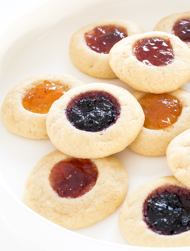 thumbprint cookies filled with different flavors of jam, arrange on a white plate