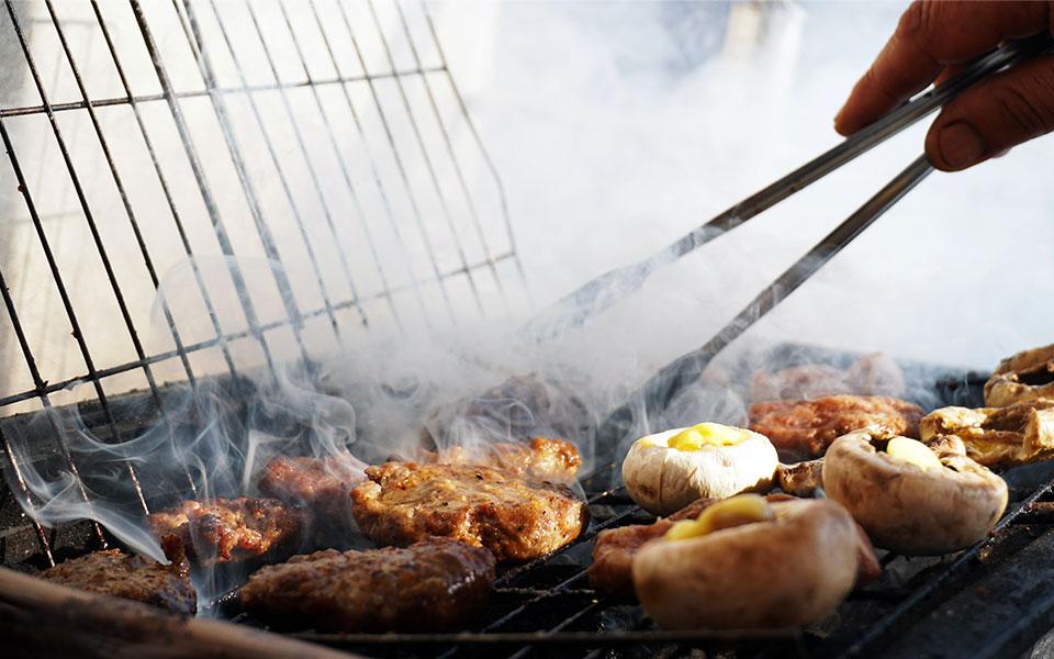 grillmaster-chef barbecued vlees en champignons op hete kolen
