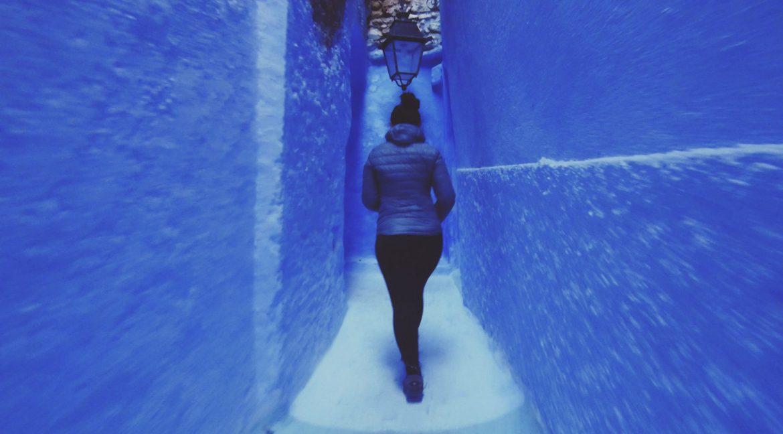 Mulher caminha nas ruelas da incrível cidade azul. Chefchauen