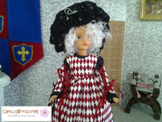 Image of Vintage Tammy doll wearing white wig, black gown, and harlequin-style pinafore