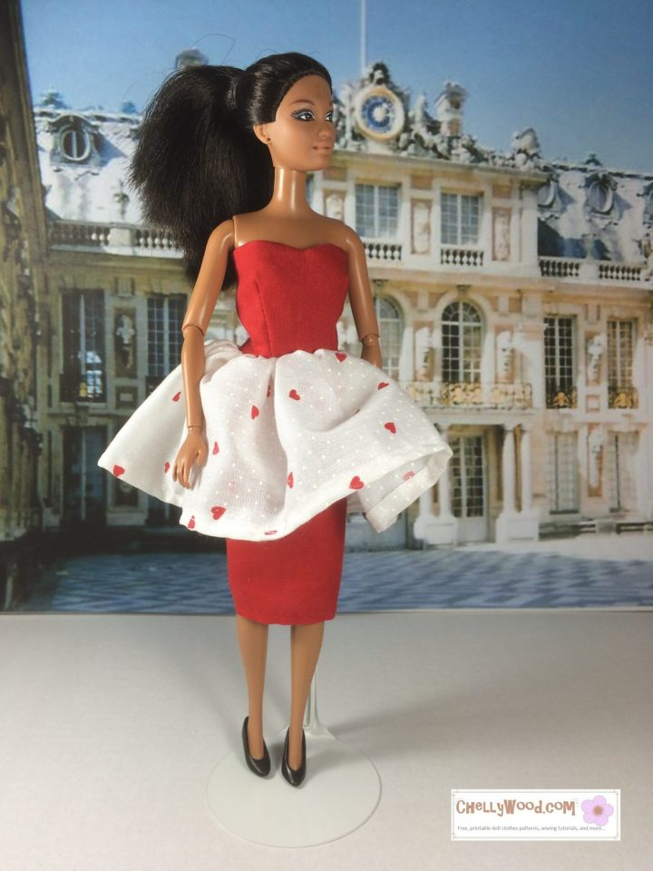 Image of African American Barbie wearing a red strapless dress with flouncy white skirting atop a pencil skirt of red. White flouncy skirt has small red hearts printed on it. This page offers a FREE Printable PDF sewing pattern for making a dress for a regular Mattel-sized Barbie Doll. The pattern and tutorial video can be found at ChellyWood.com