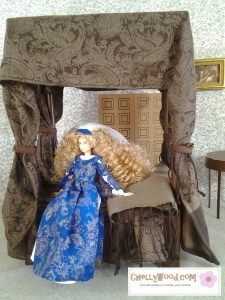 "Visit ChellyWood.com for free, printable sewing patterns to fit dolls of many shapes and sizes. Image shows Japanese Momoko doll sitting on a four-poster bed with velvety bed-curtains. Momoko Doll wears a blue and gold gown with Renaissance lace-up sleeves and a blue and white gauzy veil. Caption says, ""Chelly Wood dot com for free, printable sewing patterns and tutorials."""