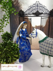 Visit ChellyWood.com for free, printable sewing patterns to fit dolls of many shapes and sizes. Image of Momoko Doll dressed in blue and gold Renaissance gown and veil, with her hands oustretched toward a Breyer model horse who wears a plaid blanket and blue harness. In the background is an iron gate which stands open, leading into a garden.