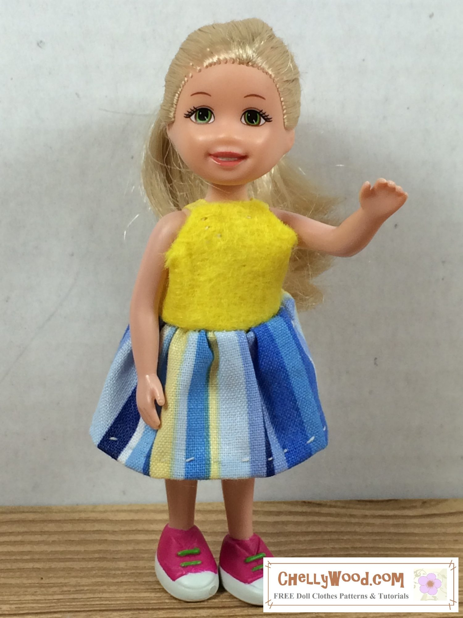 In this photograph a tiny Kelly doll raises one hand as if to wave. She wears a teeny-tiny sun dress made of yellow felt (for the bodice) and blue and yellow striped cotton (for the gathered skirt). Tiny yellow ribbons form shoulder straps.