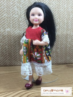 The image shows a Mattel Chelsea doll wearing a handmade doll dress in a folk dress style. Click here to download the free printable PDF sewing pattern and to view the tutorials for making this dress: https://wp.me/p1LmCj-GP1