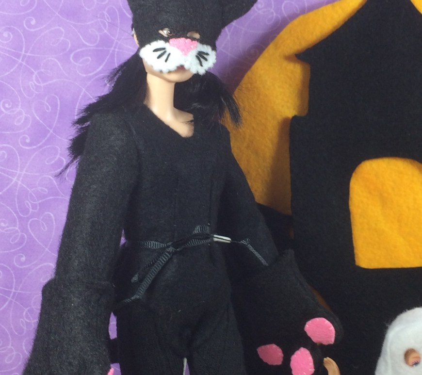 "Image of Made to Move Barbie doll wearing a handmade felt mask and cat bodysuit costume, complete with paws, tail, and tights. Overlay says, ""ChellyWood.com free printable doll clothes patterns and tutorials."""