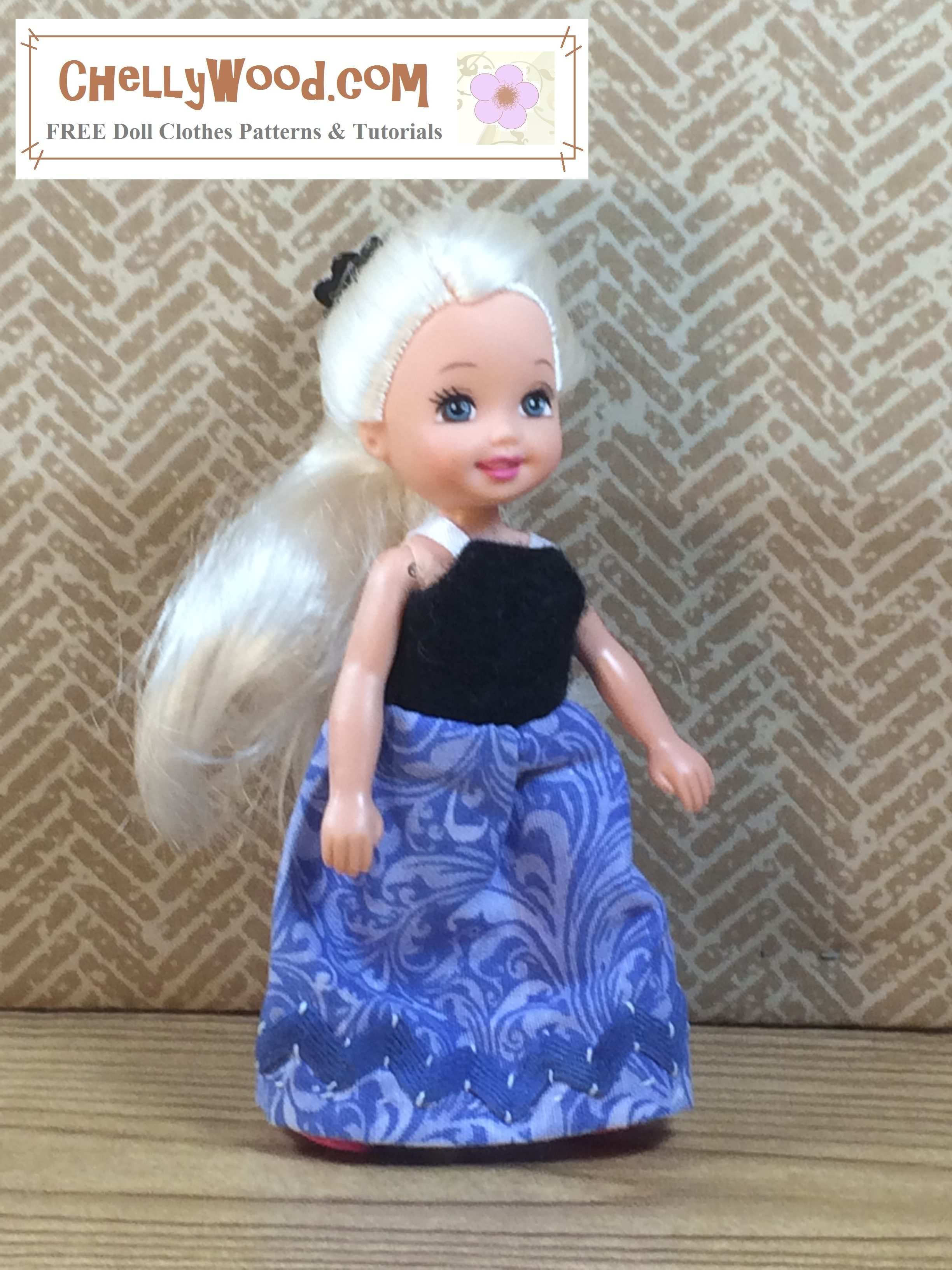 The image shows a Mattel Kelly doll with platinum blond long hair modeling a handmade evening gown. The gown's bodice is a simple sundress style, and it has been made of black felt. The skirt is a deep blue with purple and turquoise swirls. This cotton long skirt is trimmed in deep indigo blue rickrack trim. The dress has white 1/8 inch satin ribbon straps.
