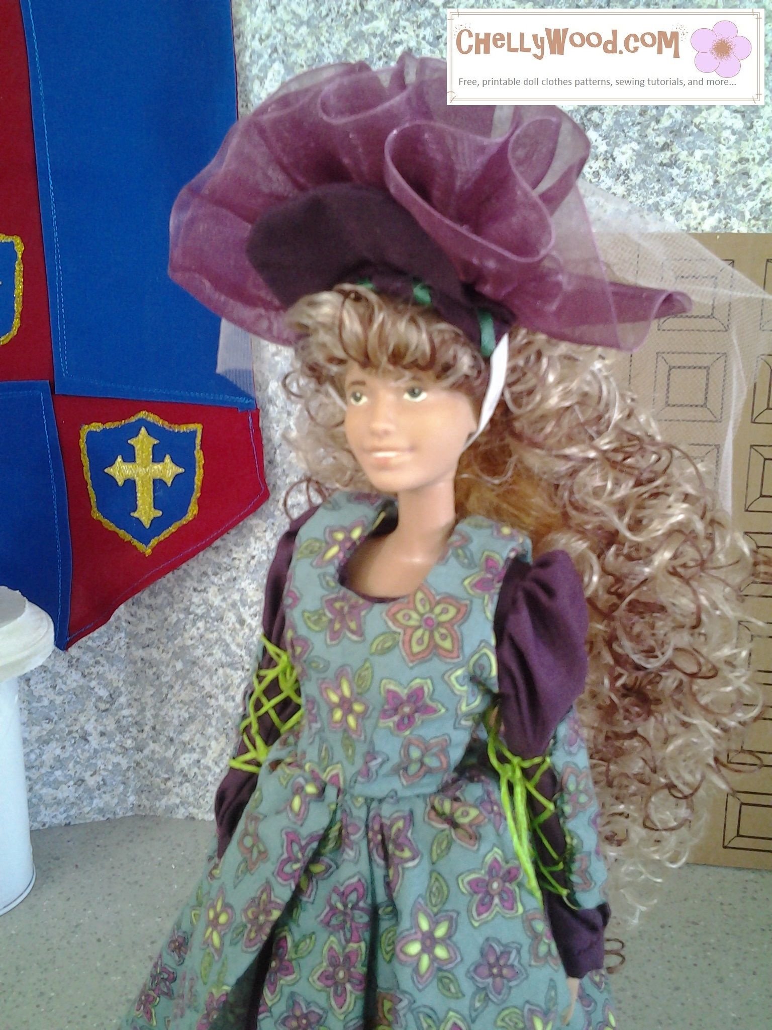 """Here we see a Mattel Barbie wearing a wig of dishwater blond curls that coil down her back. She's also wearing a slightly different version of the Basque ball gown pattern from ChellyWood.com (search for """"Basque"""" to find that yellow dress with tiny red flowers and a snood). On top of this Barbie's head is a burgundy-colored tiara that's framed in wine-colored tulle. It's held on her head by a thin piece of elastic."""