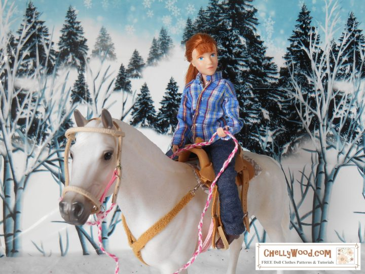 The image shows a Breyer Rider 8 inch figure on Snowball, a white horse, in a snowy mountain landscape. The horse wears a handmade saddle with bridle and breast collar. The doll or rider figure wears a handmade cotton shirt made of lightweight blue plaid fabric and a pair of denim jeans along with standard ankle-high boots. She holds the reins with a look of easy riding rhythm.