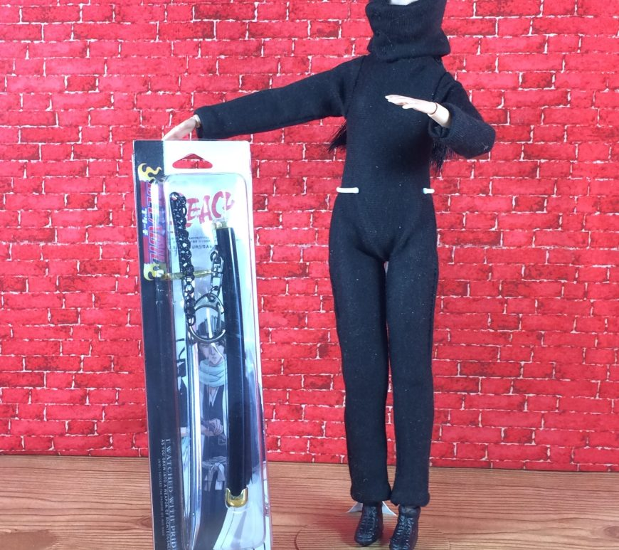 "Image shows Made-to-Move Barbie wearing a handmade Ninja costume complete with body suit, mask, and black shoes. She's holding a packaged ninja-style sword. Overlay says, ""ChellyWood.com: free printable sewing patterns for dolls of many shapes and sizes."" Doll samurai sword fits 1:6 scale."