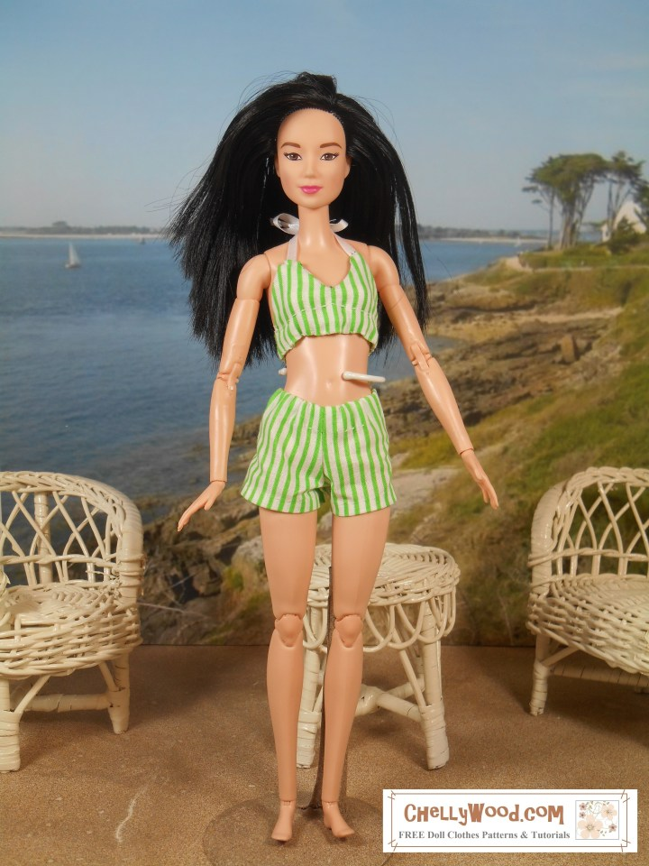 "If you'd like to make this retro Barbie bikini with ""booty shorts"" style swimsuit bottoms, please click on the link in the caption. This image shows a Made-to-Move Barbie wearing a Marilyn Monroe-style 1950s or early 1960s swimsuit / bikini with a halter style swimsuit top and booty-shorts-style swimsuit bottoms. The doll stands on sandy ground, surrounded by 1:6 scale wicker lawn furniture with a sun swept bay behind her. There's a cottage behind her on a grassy slope that leads to the beach. The watermark reminds us to visit ChellyWood.com for free printable PDF sewing patterns."