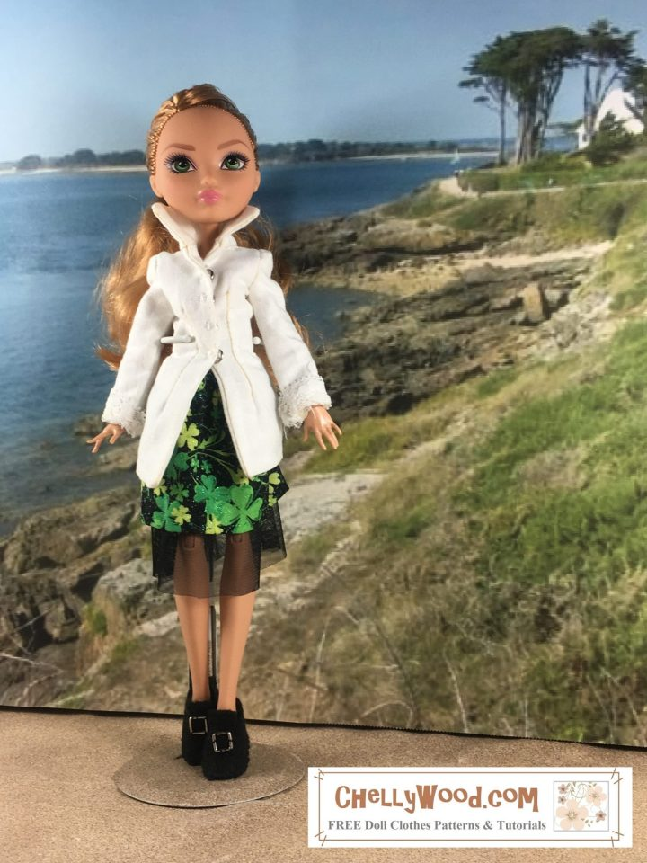 Here we see an Ever After High female doll wearing a skirt and high-collar blouse. She stands on a beach with a harbor behind her. The doll's skirt has a black tulle petticoat, and the cotton skirt over the top of the tulle is black with little shamrocks forming the print of the cotton skirt. The blouse is white and has lace cuffs. It's a long tunic, but it opens a bit at the waistline to expose the colorful skirt.