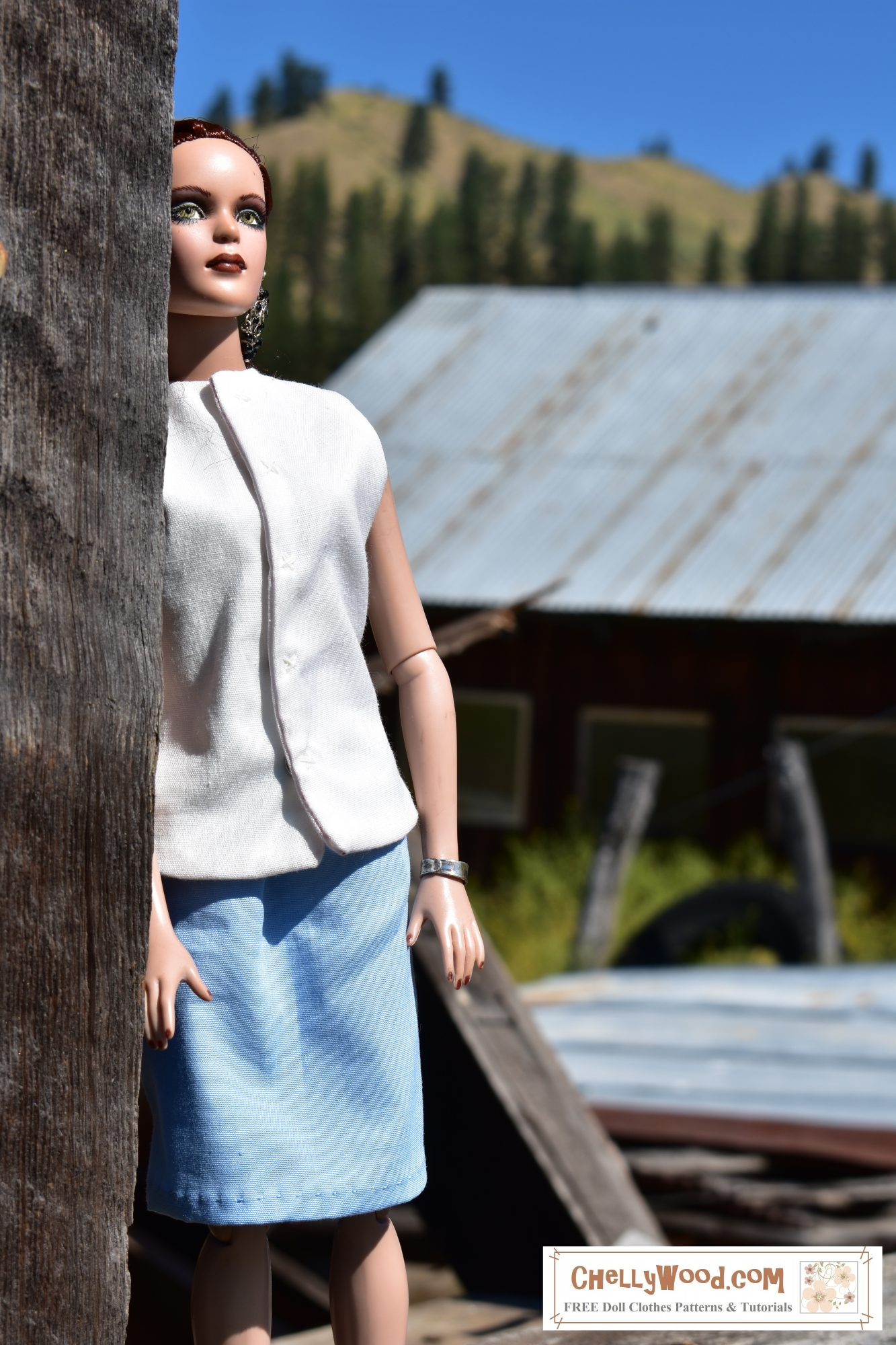 A Tonner doll with heavy eye makeup models a simple white sleeveless summer shirt and a light blue business skirt. The setting behind her shows barns in a grassy field with pine trees behind her.