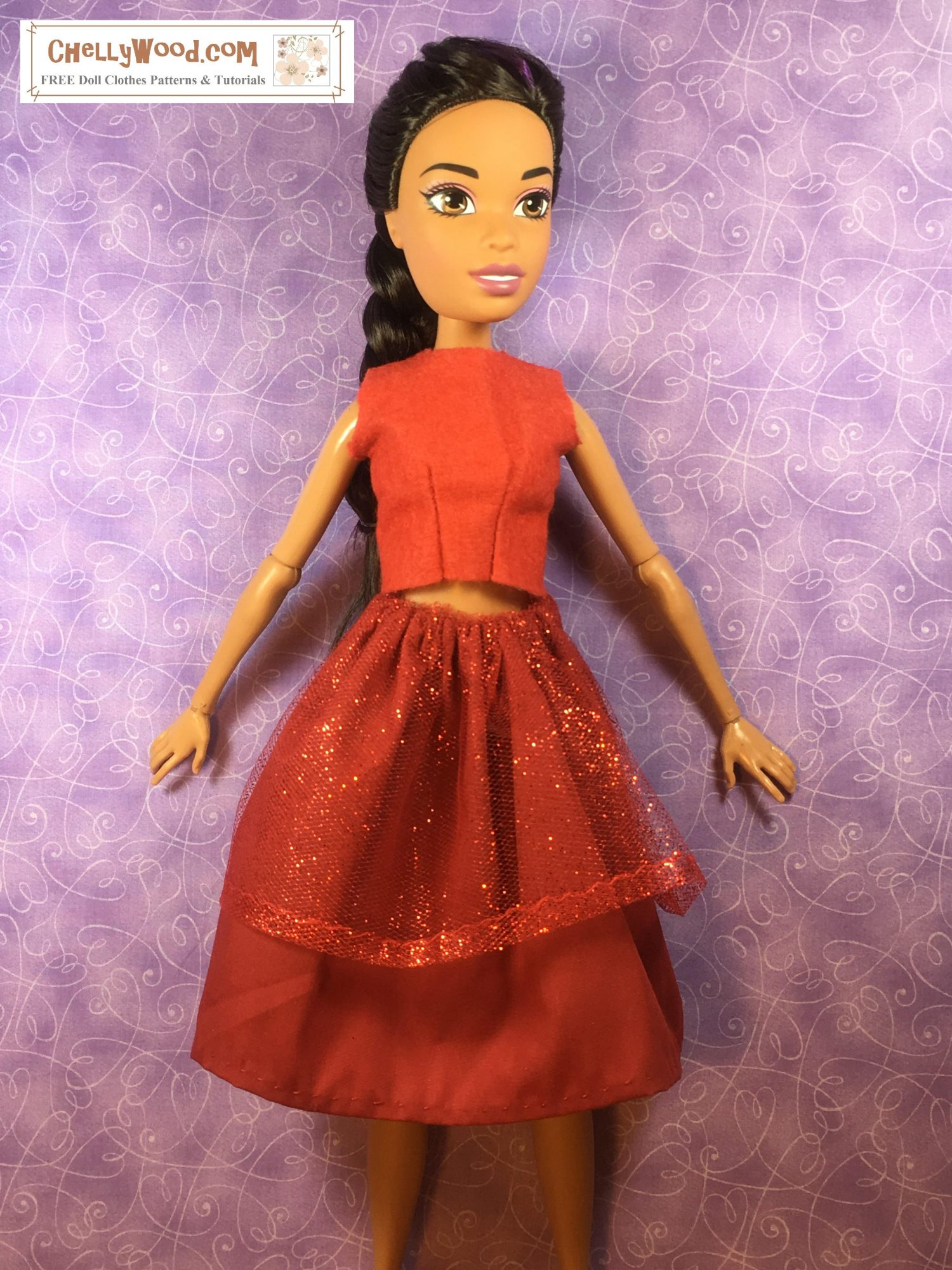 Against a purple background, the 17 inch Barbie known as Endless Hair Kingdom (Dreamtopia) Barbie models a sleeveless felt crop top and a glittery holiday skirt, all in red.