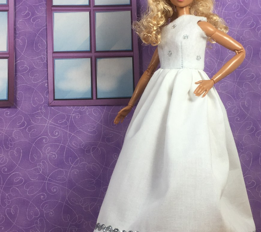 "Image shows a made-to-move Barbie from Mattel wearing a handmade wedding gown. The bodice of the gown, which is made of felt, covers one of the doll's shoulders, leaving the other exposed. The bodice is spotted with silver polka dots. The skirt is pure white and gathered, with a silvery rick-rack decorating the bottom of the skirting. Her tiny white flat shoes peek out from under the long wedding gown. She stands before a purple wall that has two simple windows looking out at a cloudy sky. The doll's hair is blond with curls, and the overlay says, ""ChellyWood.com: FREE printable sewing patterns and more."""