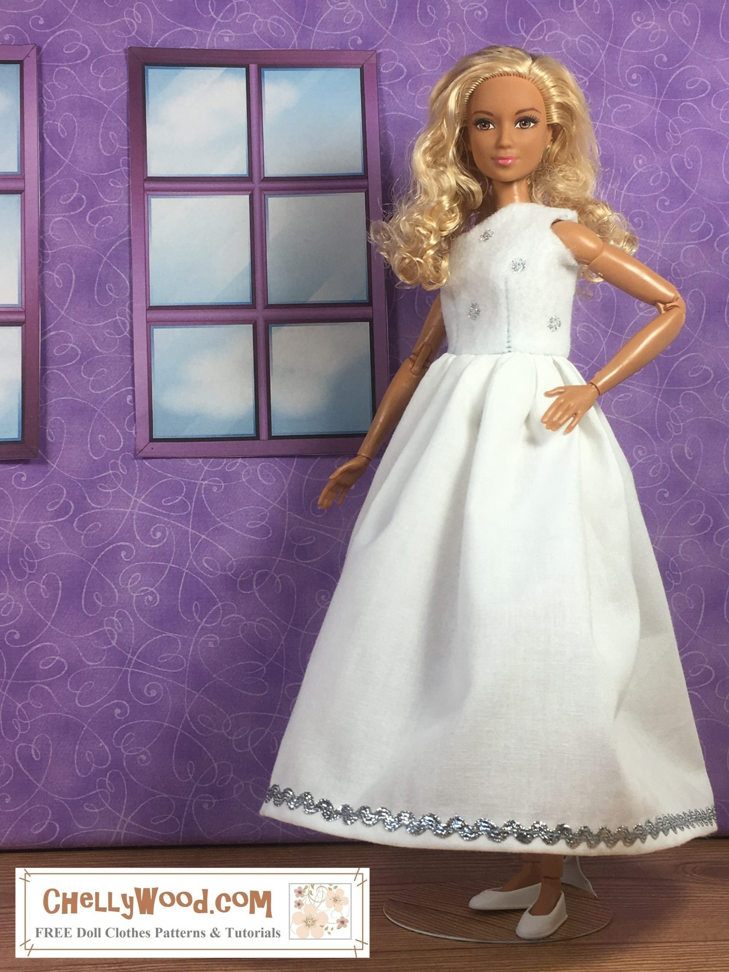 The image shows a Mattel Made to Move Barbie doll modeling a handmade wedding dress with a bodice that covers only one shoulder. The bodice is made of felt while the skirt is made of cotton. The skirt is trimmed in silver rickrack while the bodice is sprinkled with silver polka dots. The doll stands in a simple diorama with purple walls and tiny windows. If you'd like to make this doll dress, you can click on the link in the caption, and it will take you to the page where the pattern and tutorials for making this dress can be found.