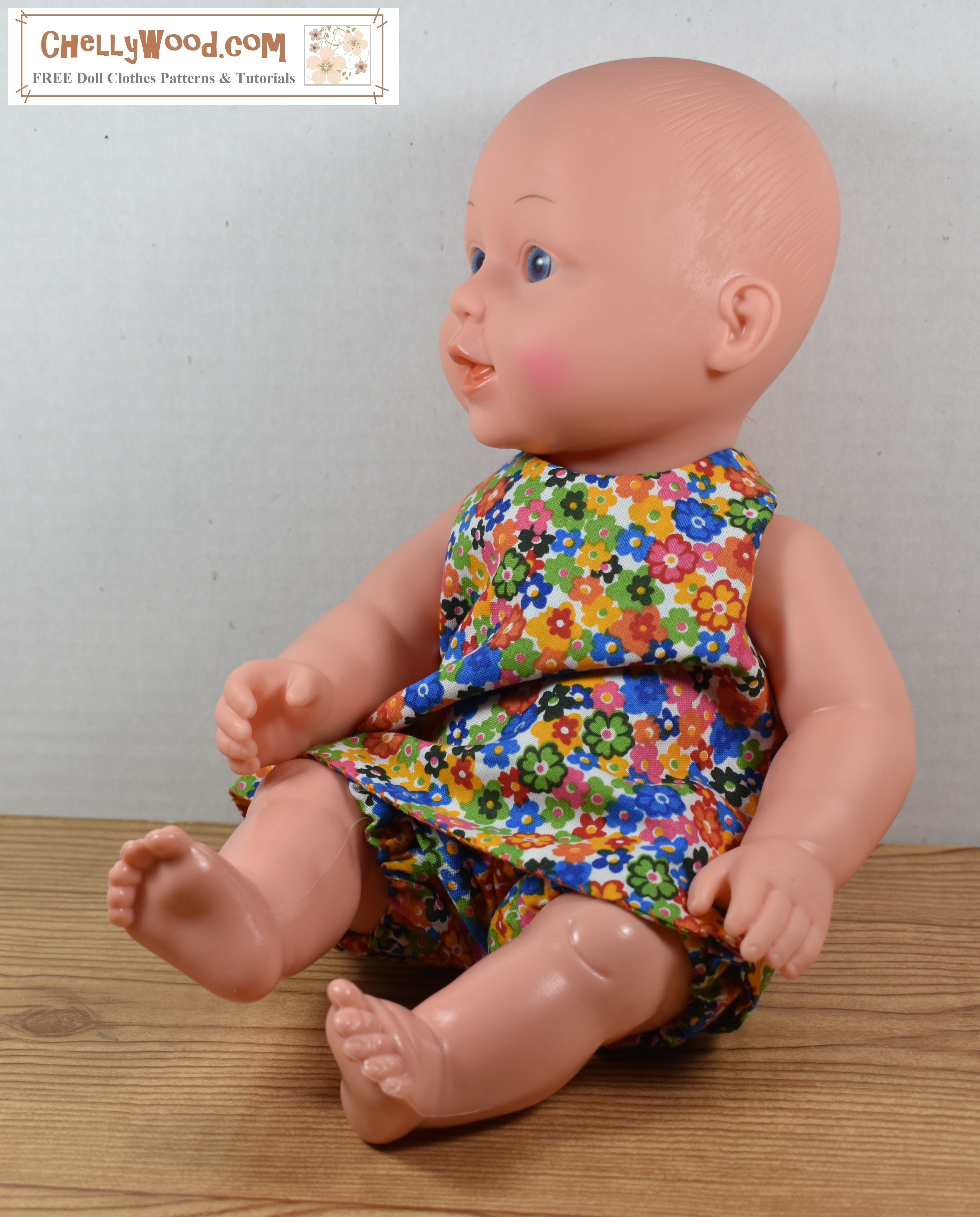 The photo shows a 12 inch baby doll modeling  a halter dress with a matching pair of bloomers in cotton floral fabric.