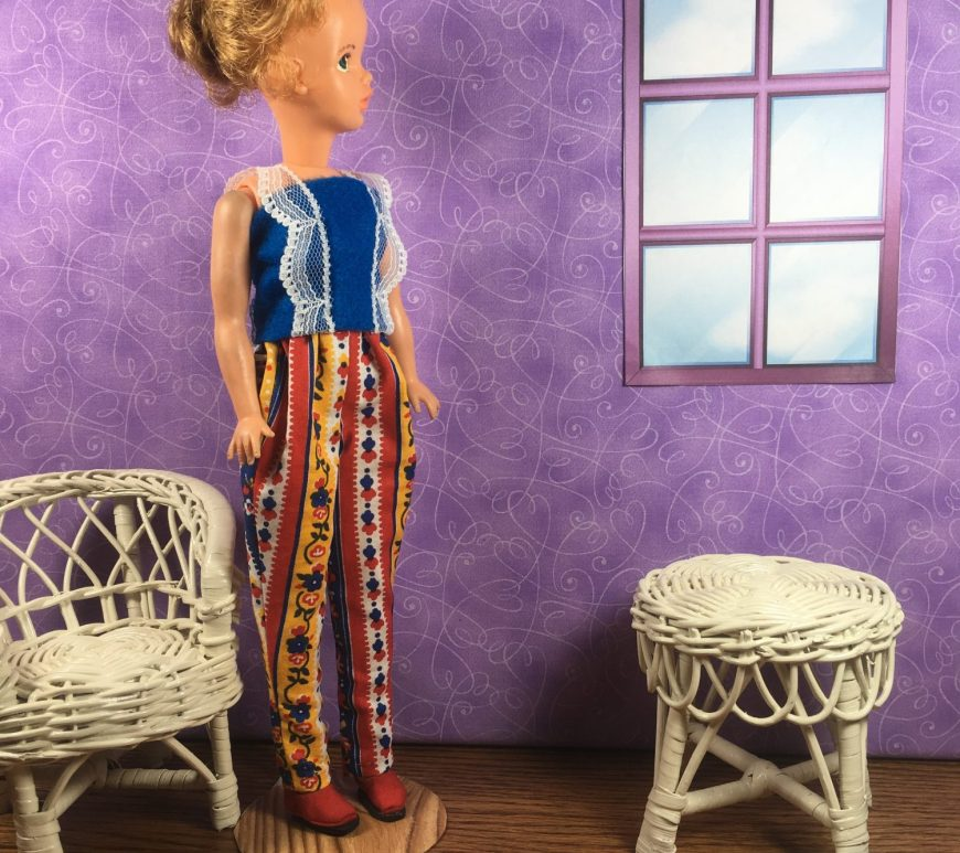 A vintage Tammy doll from Ideal wears a handmade shirt with decorative lace straps and a pair of colorful pants with an elastic waist. The shirt is a tank style top made of blue felt with white lace that forms the straps and the lace trails down the front of the shirt as well. The elastic waist pants taper at the bottom of the leg and are decorated with vertical stripes of colorful blue, red, gold, and white folk images like flowers, dots, and leaves.