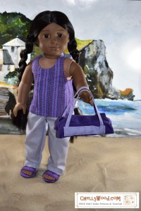 """Image shows the Kiya doll from the American Girl Doll company wearing a hand-made halter top, hand-sewn pants, and DIY sandals. She carries a hand-sewn duffle bag that matches her outfit. She stands on a sandy beach with a seascape behind her including rocky cliffs and rolling waves. Kiya looks at the camera with honest eyes. She extends one hand in which she carries the DIY duffle bag. The header for the image says, """"Purple Duffle Bag Pattern for AG Dolls FREE 2"""" and the watermark says, """"ChellyWood.com: FREE doll clothes patterns and tutorials."""" In fact, if you go to ChellyWood.com, you can download the free, printable sewing pattern for this duffle bag (and the other American Girl -sized doll clothes patterns for the other items of clothing she wears) and all patterns at ChellyWood.com are free and come with a free tutorial video showing how to make the clothing item (including this duffle bag or overnight bag for dolls)."""